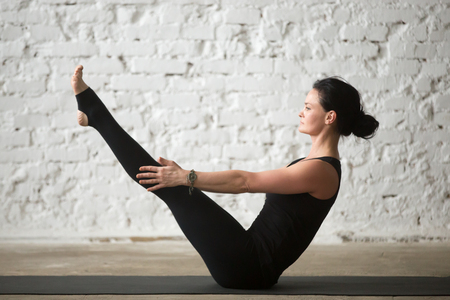 Photo pour Young yogi attractive woman practicing yoga concept, stretching in Paripurna Navasana exercise, balance pose, working out, wearing sportswear, black tank top and pants, full length, loft background - image libre de droit