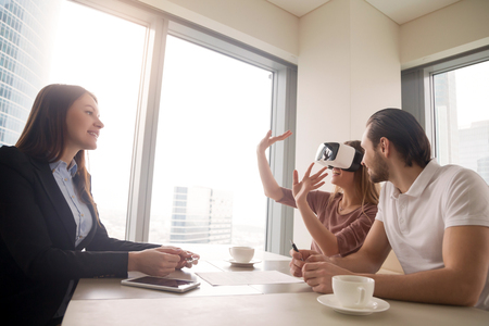 Photo pour Young woman wearing virtual reality glasses or goggles, couple using head-mounted display for real estate tours, excited by participation effect, virtually discover new flat, buy and sell homes in VR - image libre de droit