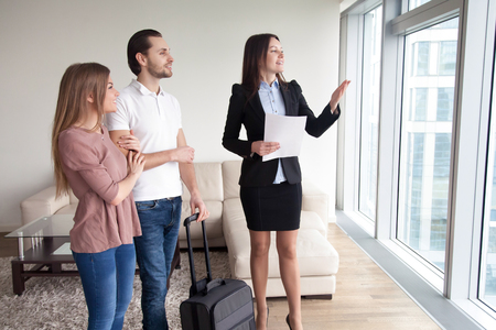 Photo pour Happy young couple travelers moving in new rented own apartment, standing by the window enjoying view, meeting with female real estate agent showing flat for rent, telling about nearby attractions - image libre de droit