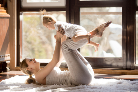 Photo for Young mother working out wearing white sportswear,  exercising at home with baby daughter, leg lifting with kid as a weigh, exercising and bonding with child, enjoyment. Healthy lifestyle concept - Royalty Free Image