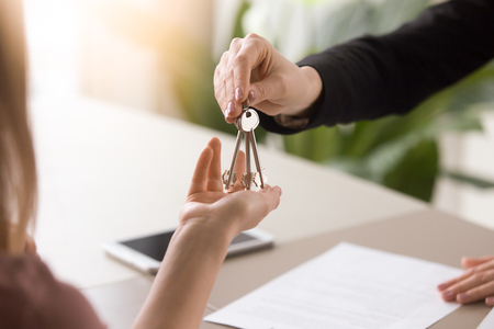 Foto de Young lady taking keys from female real estate agent during meeting after signing rental lease contract or sale purchase agreement. Independent woman purchasing new home, close up view - Imagen libre de derechos