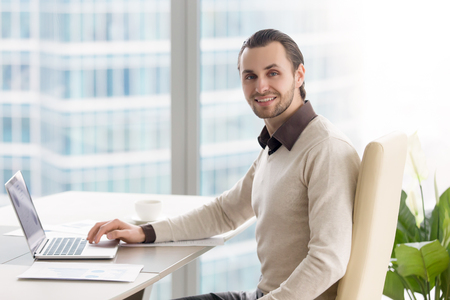 Foto de Portrait of handsome confident young businessman sitting at the office desk. Smiling happy executive officer working with laptop and graphs at workplace, successful manager looking at camera - Imagen libre de derechos