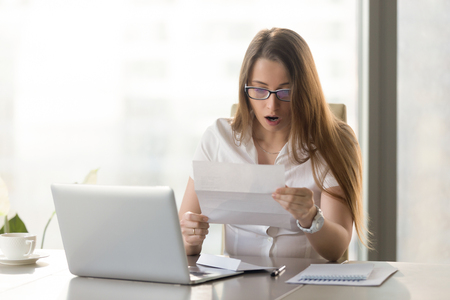 Photo for Surprised young businesswoman reading letter at the desk in front of laptop. Woman feels shocked after receiving unexpected news in written message. Female entrepreneur holds notice about loan debt - Royalty Free Image