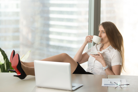 Photo for Businesswoman drinking coffee with legs on desk. Girl resting at the desk with cup of tea. Confident lady takes a break at work. Successful female entrepreneur relaxing after productive day in office - Royalty Free Image