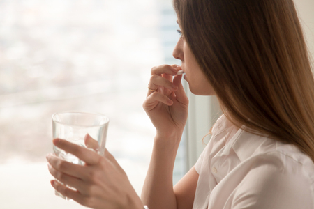 Photo pour Young woman takes white round pill with glass of water in hand. Stressed female looking in window and drinking sedated antidepressant meds. Woman feels depressed, taking drugs. Medicines at work - image libre de droit