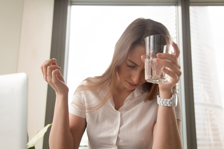 Foto de Businesswoman suffering from head ache at workplace. Stressed young woman puts glass of water to forehead and holding pill in hand. Female feeling sudden sickness at work. Addiction after medicines - Imagen libre de derechos