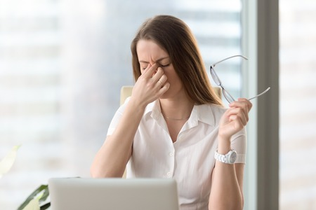 Foto de Tired businesswoman holding eyeglasses and massaging nose bridge. Girl feeling discomfort from long wearing glasses at workplace. Exhausted female office worker gather herself for completing work - Imagen libre de derechos