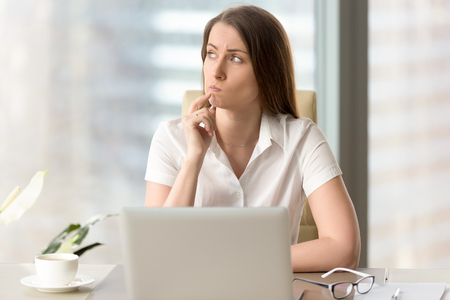 Photo pour Woman with pensive facial expression looking aside while sitting at workplace. Unsure businesswoman thinking about difficult question. Female office worker doubted because of uncertain situation - image libre de droit
