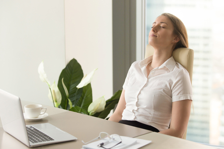 Foto de Businesswoman takes short time-out in office work. Beautiful girl lying relaxed on back chair. Female entrepreneur resting at workplace. Comfortable office furniture for long work in sitting position - Imagen libre de derechos