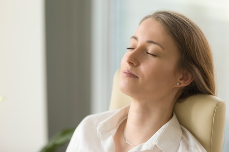 Foto de Tired woman lying on back chair with closed eyes. Businesswoman doing deep relaxation exercises during hard working day. Beautiful girl dreaming about future in office. Short meditation at workplace - Imagen libre de derechos