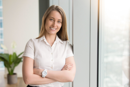 Photo pour Head shot portrait of smiling attractive young woman with arms crossed looking at camera. Successful positive entrepreneur posing near window. Happy businesswoman works at office, feeling optimistic - image libre de droit