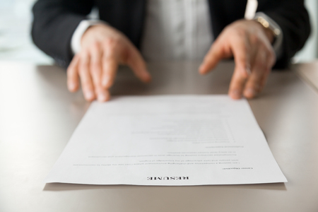 Photo for Resume document with guys hands in background. Recruitment manager reads resume. Job applicant offers CV to recruiter at interview. Employer examines achievements of new company worker. Close up photo - Royalty Free Image