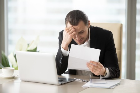 Photo pour Stressed businessman upset because of bank letter with warnings about loan debt. Sad guy worries about financial problems. Office worker sitting shocked at desk after receives notice of dismissal - image libre de droit
