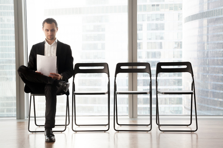 Photo pour Confident job applicant reads resume while sitting on chair in row in office and waiting his turn on interview. Young guy wearing suit prepares for recruitment meeting with employer in waiting room - image libre de droit