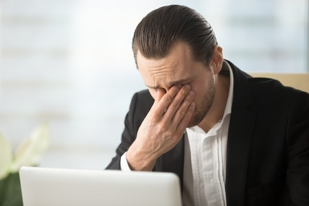 Photo pour Frustrated businessman feels pain in eyes because of eyesight overstrain after long computer work. Tired young man massaging eyes in front of laptop. Eyes fatigue, headache or dizziness at workplace - image libre de droit