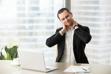 Foto de Businessman feeling pain in neck after sitting at desk. Tired man suffering of office syndrome after long hours work on computer. Entrepreneur massaging his tense neck muscles. Gymnastics at work - Imagen libre de derechos