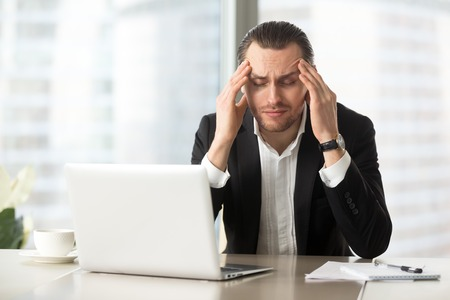 Foto de Frustrated man squeezes temples with hands at desk in front of laptop. Tired businessman suffers from headache at workplace. Entrepreneur feels chronic fatigue, work stress because of business problem - Imagen libre de derechos