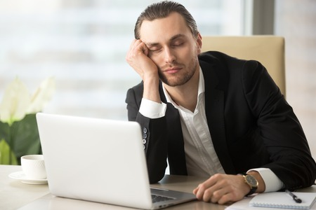 Photo pour Young man dozing with head on hand while sitting at desk with laptop in office. Businessman sleeping at workplace in morning after weekend party day before. Tired male entrepreneur slumbers at work - image libre de droit