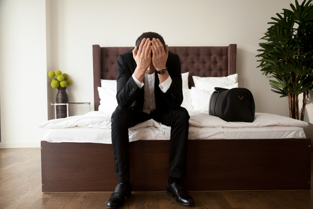 Photo pour Upset stressed man in business suit sitting with head in hands on bed edge beside  handbag with belongings. Leaving home because of divorce, problems in relations or business, loss through loan debts - image libre de droit