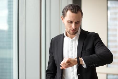 Photo pour Busy businessman looking at wristwatch while hurrying on meeting in office. Young man in business suit checks time left to end of work day. Entrepreneur worried, lack of time on important work tasks - image libre de droit