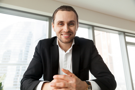 Foto de Portrait of young attractive man in suit sitting at desk looking in camera with smile. Businessman feels positive emotions during negotiations with partners. Boss on interview with job applicants - Imagen libre de derechos