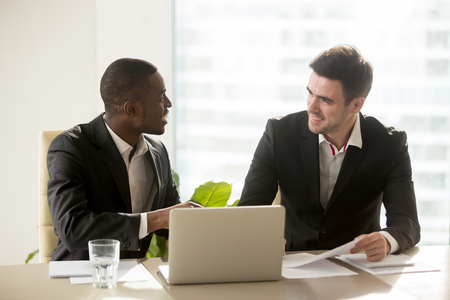 Photo pour Two accomplished multiracial businessmen discussing idea new business projects at office desk, multi ethnic business group having pleasant funny conversation indoors, running company together - image libre de droit