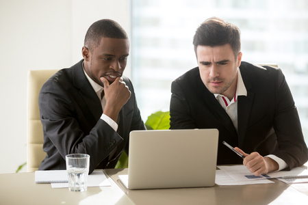 Foto de Two businessmen on meeting in formal wear looking at laptop screen, focused on presentation, thoughtful concentrated on task, trying to solve problem, analyzing market, considering business offer - Imagen libre de derechos