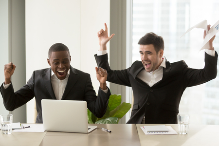 Photo for Two happy businessmen in suits raising hands near laptop, multicultural business group celebrate victory, stock trading success, impressive achievements, great luck, win important contract, we did it - Royalty Free Image