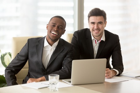Photo pour Two cheerful businessmen wearing suits sit at the desk, looking at camera, friendly entrepreneurs ready for collaboration, running successful company together, multiracial business partners portrait - image libre de droit