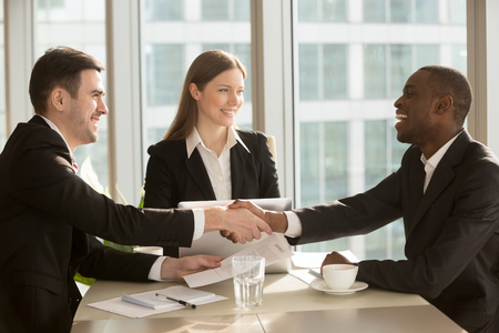 Photo for Happy smiling black and white businessmen handshaking after signing contract at multi-ethnic meeting with businesswoman, multiracial partners shaking hands, sealing closing deal with satisfied client - Royalty Free Image