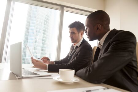 Foto de Side view of two multiracial business partners in formal wear discussing document on meeting sitting at desk, black and white businessmen studying contract terms, explaining idea, planning project - Imagen libre de derechos