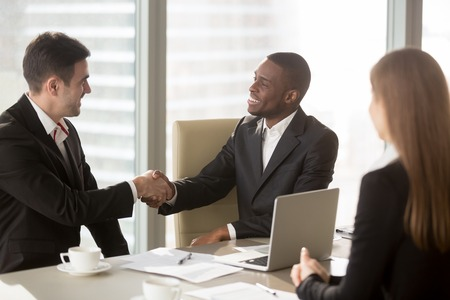 Photo for Two cheerful businessmen handshaking at formal meeting, starting finishing negotiations, african entrepreneur wearing black suit white shirt and caucasian partner shake hands, making profitable deal - Royalty Free Image