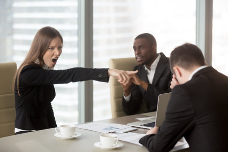 Foto de Angry female furious boss scolding employee at mixed-race team meeting, firing dismissing depressed office worker for failure, bad work results, being ineffective, pointing finger, its your fault - Imagen libre de derechos