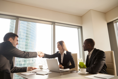 Photo for Cheerful female and male caucasian partners handshaking over office desk, multi-ethnic meeting with afro american businessman, concluding successful deal, forming good partnership, reaching agreement - Royalty Free Image