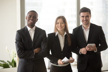 Photo pour Cheerful businesswoman in formal wear standing between two confident businessmen posing for camera, multi-ethnic team portrait, motivated professional consultants, board of directors, business group - image libre de droit