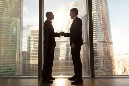 Photo pour Two smiling young black and white businessmen handshaking standing near big window with city buildings outside, confident caucasian and afro american partners form good relations, reach agreement - image libre de droit