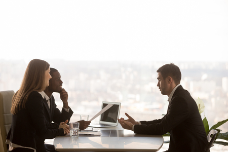Photo for Friendly attentive hr managers interviewing vacancy applicant, multi-ethnic partners discussing new project idea sitting at office desk with cityscape outside, big window at background, side view - Royalty Free Image