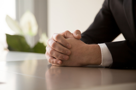 Foto de Close up of male clasped hands clenched together on table, businessman preparing for job interview, concentrating before important negotiations, thinking or making decision, business concept - Imagen libre de derechos