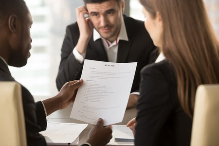 Foto de Employers or recruiters holding reviewing bad poor cv of unemployed worried nervous applicant waiting for result, employment and recruitment concept, rejected job application, failed interview, close up - Imagen libre de derechos