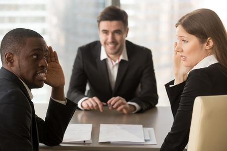 Photo pour Multiracial confused employers covertly discuss job applicant, hide face with hands, look puzzled bewildered, secretly whisper during failed interview, bad negative first impression, make decision - image libre de droit