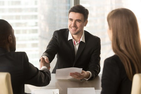 Photo for Happy applicant greeting employers at job interview, cheerful satisfied partners shaking hands, making deal agreement with friendly handshake at meeting, successful effective negotiations, get a job - Royalty Free Image