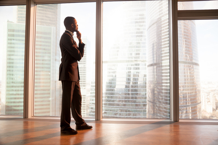 Foto für Young afro american contemplative businessman stands in office with hand on chin, looks through big window at the city, african entrepreneur enjoys sunset, rests after work, gets business inspiration - Lizenzfreies Bild