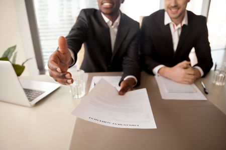 Photo pour Close up of black businessman offering job, reaching out employment agreement to successful applicant, labor contract of work, extending hand for handshake, hiring new employee, getting job - image libre de droit
