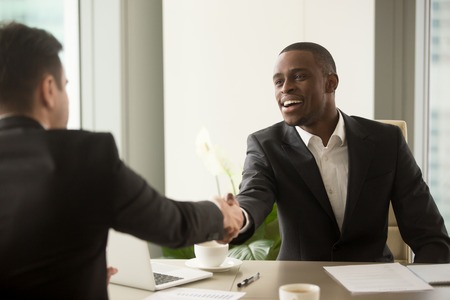 Photo for Two multicultural businessmen handshaking over desk, attractive african entrepreneur shaking hand of caucasian client, start finish negotiations, establishing multi-ethnic partnership, making deal - Royalty Free Image