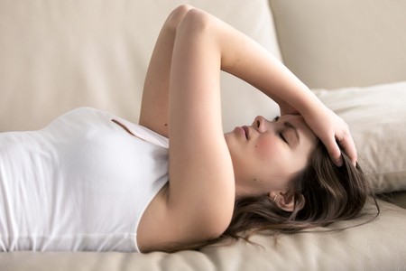 Photo pour Woman lying on sofa having headache. Stressed girl suffering of fatigue, migraine, trying to cope with nervous tension, worries because of problems, unwanted pregnancy, negative thoughts and emotions - image libre de droit