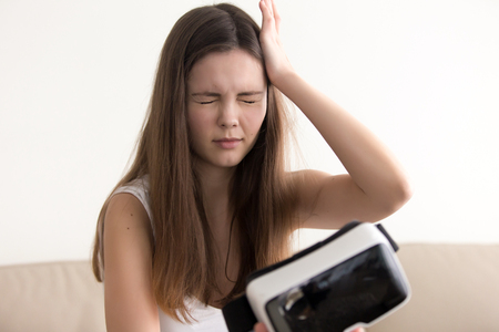 Photo pour Teenage girl feels dizziness or headache after using virtual reality glasses. Woman suffers from eyes discomfort when took off VR headset. Negative side effect of being in virtual reality. VR sickness - image libre de droit