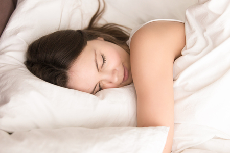 Photo pour Young woman napping while hugging soft pillow, resting in cozy bed with fresh white sheets, smiling in her sleep. Healthy sleep, deep relaxing and strength renewal after hard work week concept - image libre de droit