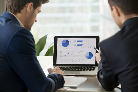 Photo pour Rear view at two businessmen analyzing stats financial data on pc laptop, pointing at screen with rising graph and charts, discussing company growth, using easy accounting software for small business - image libre de droit