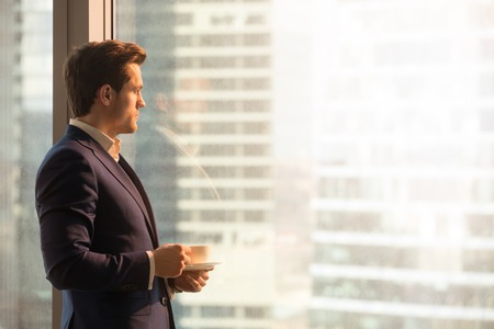 Foto de Side view of serious pensive director of prosperous company enjoying cup of coffee in the morning, thoughtful businessman in suit looking through big office window at dawn sunrise city, copy space - Imagen libre de derechos