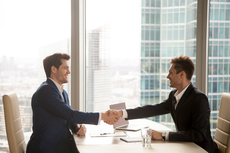 Photo for Two happy satisfied businessmen shaking hands over desk after successful negotiations, closing sealing deal, big window city building at background, smiling partners binding agreement with handshake - Royalty Free Image